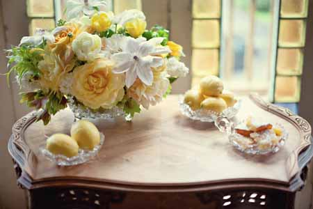 flower centerpiece with yellow garden roses, ranunculus, white clematis