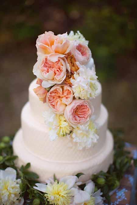 Peach garden roses decorate a wedding cake