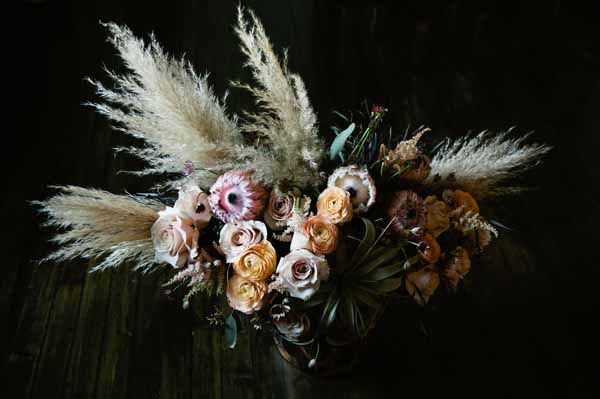 Flower centerpiece of peach ranunculus, pink fuzzy protea, pink roses, airplants