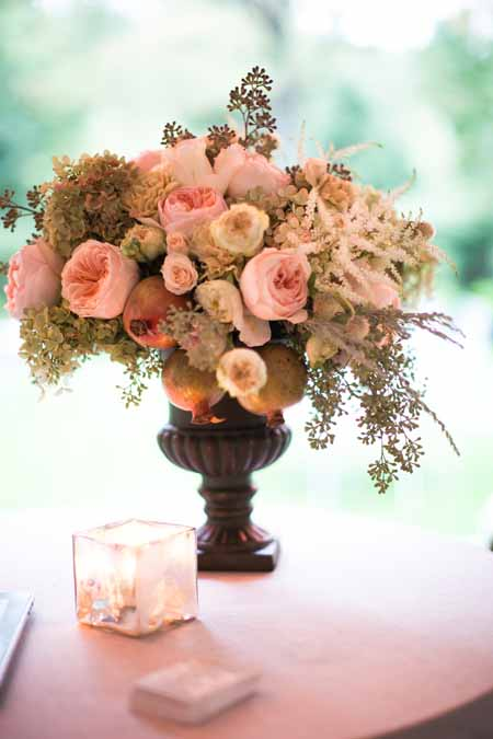 Floral design in a urn with pink garden roses, pomegranates and seeded eucalyptus