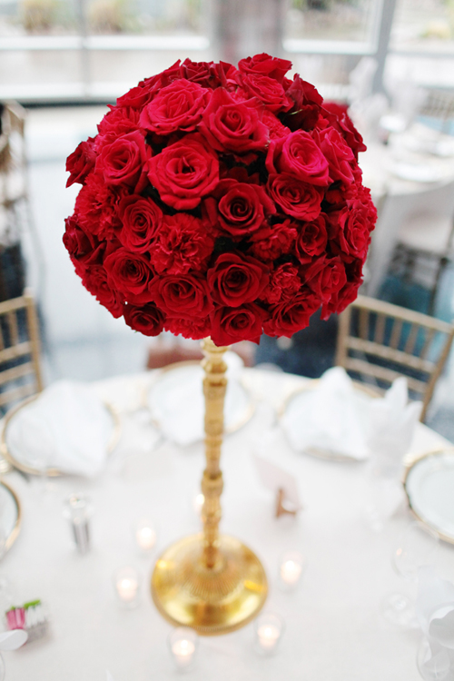 gold candelabra holding elevated red centerpiece