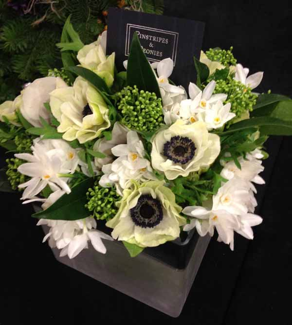 white flower arrangement anemones paperwhites and skimmia