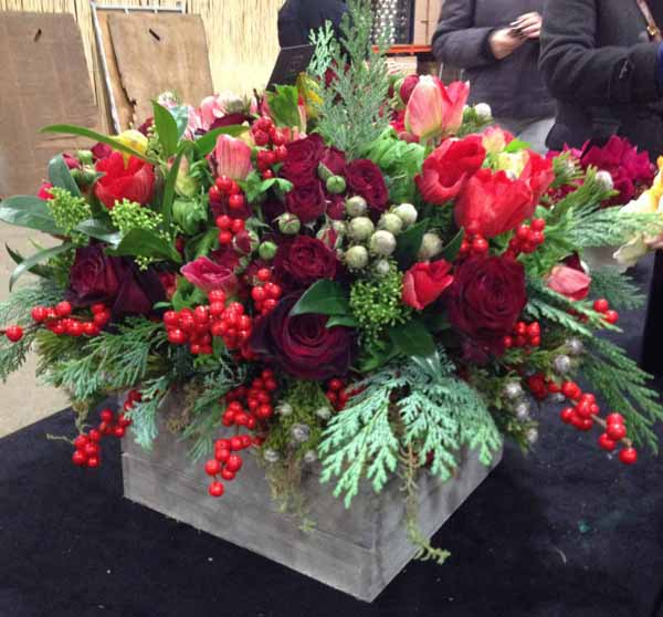 red flower arrangement anemones red rose illex berries